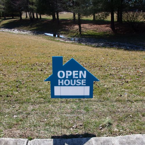 Blue house sign staked into the ground