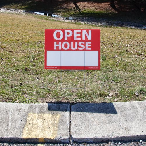 Red open house sign displayed in the ground